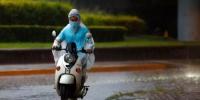 资料图:市民在雨中骑行。 中新社记者 富田 摄 - 中国新闻社河北分社